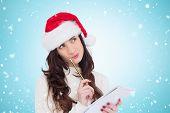 Festive brunette thinking about her christmas list against blue vignette
