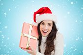 Festive brunette holding gift against blue vignette