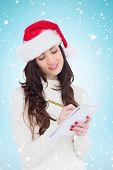 Festive brunette writing her christmas list against blue background with vignette