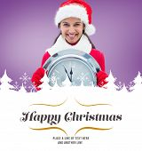 festive brunette holding clock against border