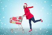 Festive brunette pushing trolley full of gifts against blue vignette