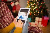 Redhead woman sitting on couch using tablet at christmas at home in the living room