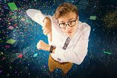 Geeky businessman pointing to watch against colourful fireworks exploding on black background