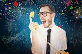 Geeky businessman shouting at telephone against colourful fireworks exploding on black background