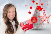 Girl holding gift against blurry christmas tree in room