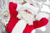 Happy santa lying and relaxing against christmas decorations hanging from branch