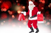 Smiling santa claus holding shopping bags against red glowing dots on black