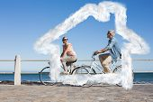 Happy casual couple going for a bike ride on the pier against house outline in clouds