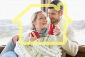Loving couple in winter wear drinking coffee against window against house outline