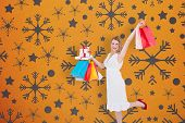 Elegant blonde with shopping bags and gifts against snowflake wallpaper pattern