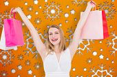 Young woman holding up shopping bags against snowflake wallpaper pattern