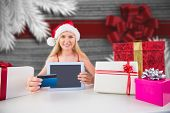 Festive blonde shopping online with tablet pc against festive bow over wood