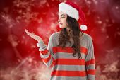 Festive brunette holding hand out against blurred christmas background