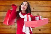 Smiling brunette holding christmas gifts against blurred wooden planks