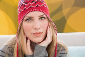 Woman wearing hat against blurry yellow christmas light circles