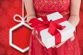 Pretty woman in red dress offering present against blurred christmas background