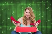 Woman holding pair of shoes discovered into the box against blurred stars on planks