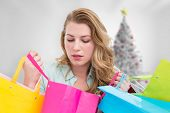 Blonde woman opening gift bag and looking on it against blurry christmas tree in room