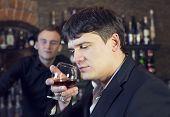 man drinking brandy near the bar