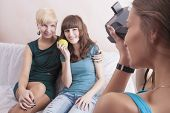 One Caucasian Girl Photographs Her Girlfriends Sitting Together Indoors