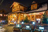 ZAKOPANE, POLAND - DECEMBER 6, 2014: Traditional cottage house on the Krupowki street in Zakopane. Krupowki street is the main shopping area and pedestrian promenade in the center of Zakopane, Poland.