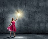 Young attractive woman in red dress touching light spot