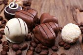 Different chocolates with coffee beans on wooden textured background