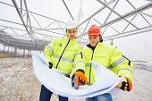 male engeneers construction foreman managers outdoors indoors at building site with blueprints