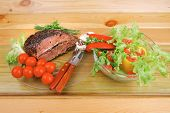 grilled beef sliced on transparent plate with salad bowl