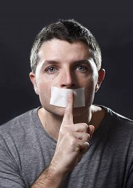 picture of freedom speech  - attractive young man with mouth sealed on duct tape to prevent him from speaking keeping him mute and censored in freedom of speech and expression concept - JPG