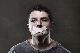 stock photo of freedom speech  - attractive young man with mouth sealed on duct tape to prevent him from speaking keeping him mute and censored in freedom of speech and expression concept - JPG