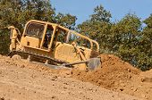 stock photo of bulldozers  - Large bulldozer moving rock and soil for fill for a new commercial development road construction project - JPG