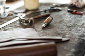 picture of wood craft  - Leather crafting tools on working desk with a low depth of field - JPG