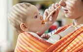stock photo of feeding  - Young mother feeding her little daughter that she has in a baby carrier - JPG