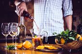 stock photo of sangria  - Man pouring red wine into a carafe, making sangria for home party, home kitchen interior. Homemade food and drinks ** Note: Soft Focus at 100%, best at smaller sizes - JPG