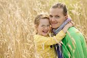 pic of bonding  - Caucasian mother and daughter hugging smiling and sharing a tender bonding moment amongst meadow grass. Mothers day concept. Serenity and tranquility. ** Note: Shallow depth of field - JPG