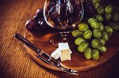 picture of knife  - A glass of brandy, grapes and brie cheese with a knife on the board, home kitchen.