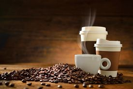 stock photo of takeaway  - Cups of coffee with smoke and coffee beans on old wooden background - JPG