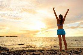 stock photo of sea life  - Freedom winning woman cheering at sunset beach - JPG