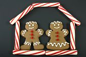 stock photo of gingerbread house  - gingerbread man and woman in a candy house on black background - JPG