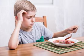 foto of fussy  - Unhappy picky child eating creamy tomato soup - JPG