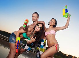 picture of pistols  - Group of young joyful young people playing with water pistols on the beach  - JPG