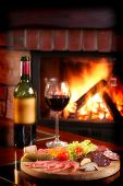 stock photo of cozy hearth  - Wine bottle and partially filled glass with assorted food on a wooden serving plate - JPG