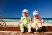 Two five months old brother twins sitting on a beach jetty