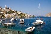 Boats in bay and houses on Symi island, Greece