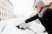 stock photo of ice-scraper  - woman removing snow from car window - JPG