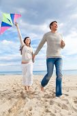 stock photo of woman dragon  - Happy outdoor autumn spring couple embracing and running on beach  a kite fly - JPG