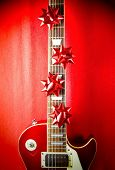 A red vintage solid body electric guitar with red ribbon bows on fretboard. A concept image for Christmas and holiday season music event.