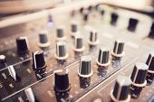 Close up of knobs on audio console poster
