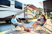 Young Couple Sits On Chairs Near Camping Trailer And Car poster